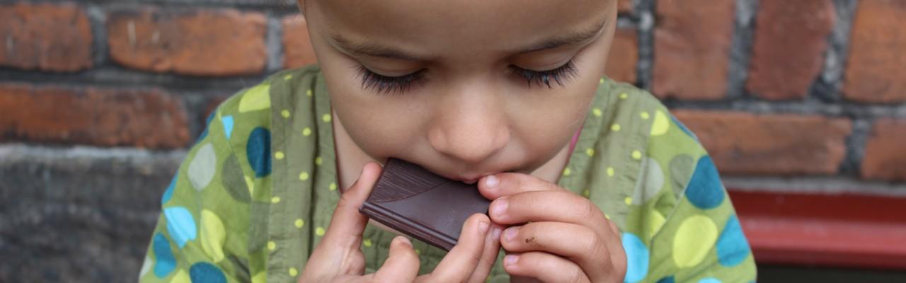 Lille pige smager på mørk chokolade. Foto: Patricia deCosta